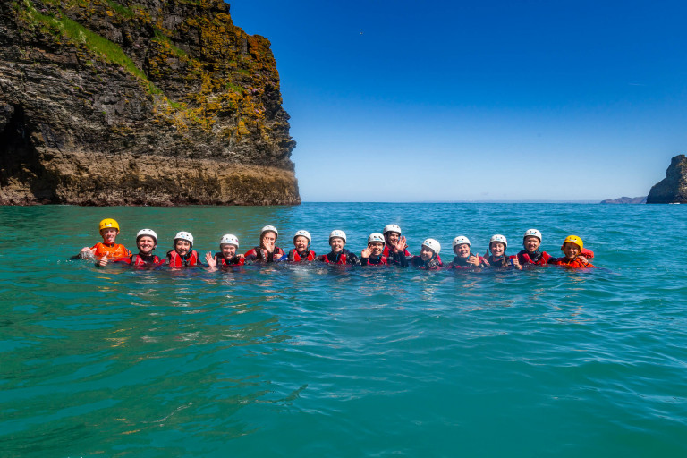 group of people in sea waving at camera while coasteering near Bude with OA Surf Club