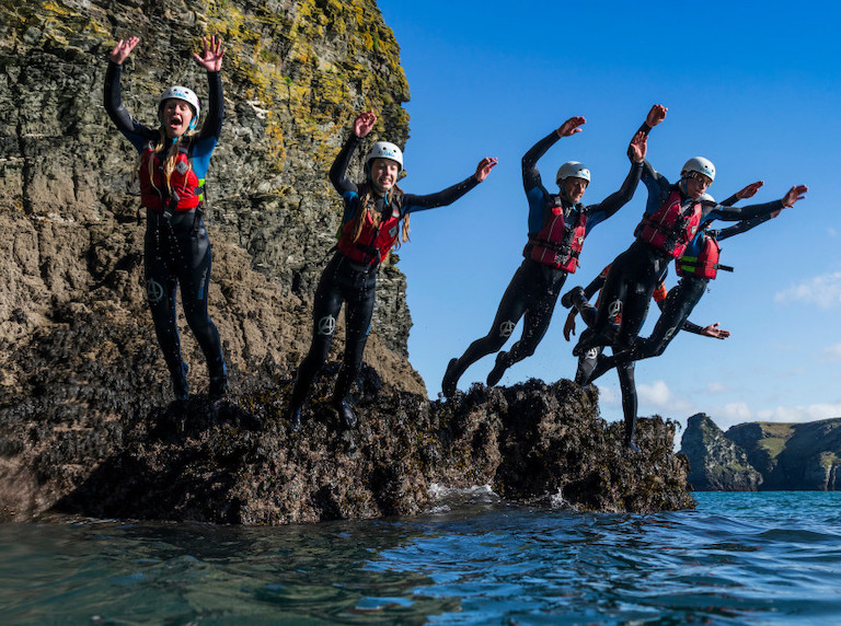 group of people jumping off rocks while coasteering wearing wetsuits, buoyancy jackets and helmets