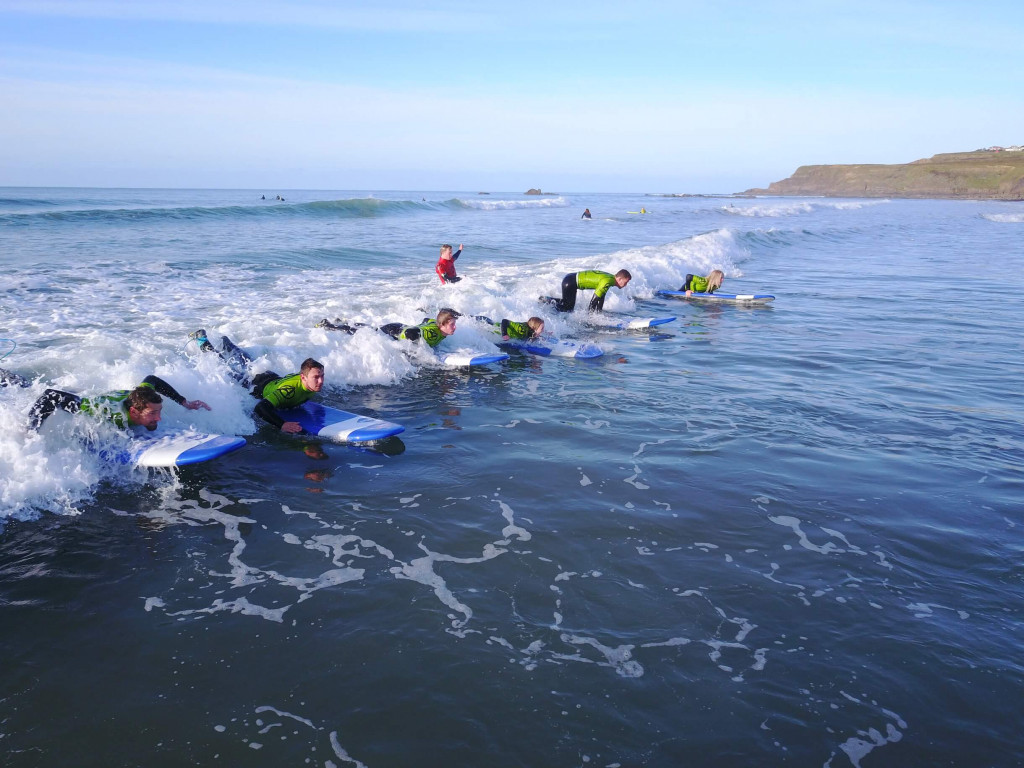 group riding the wave during a beginner surf lesson at Widemouth Bay