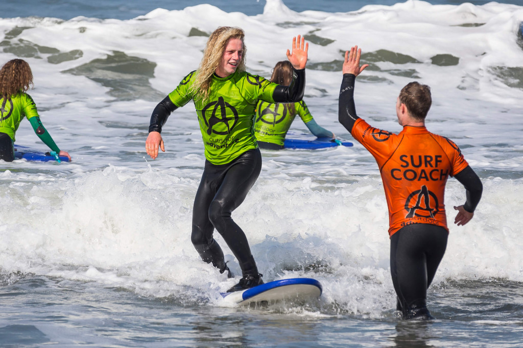 man irding wave whilst standing up on surf board and have a surf lesson near Bude