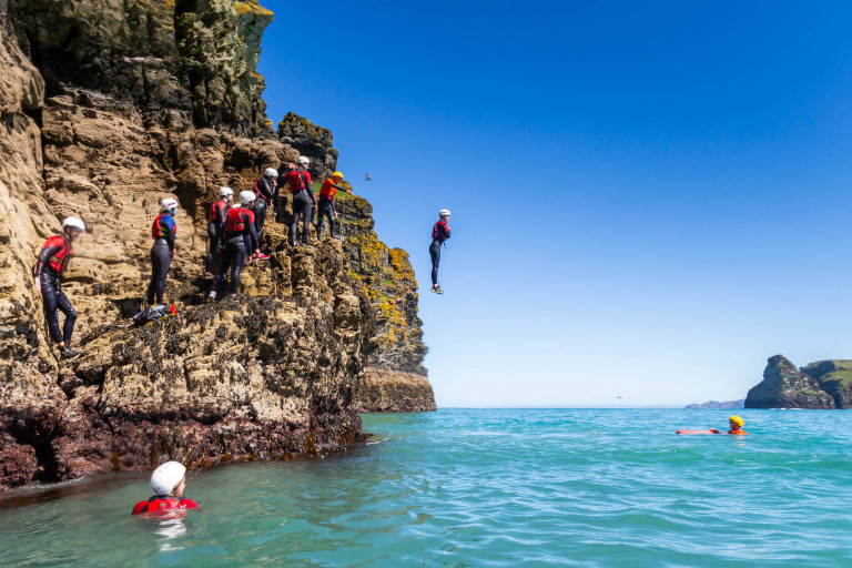 person jumping off the rocks into the sea while coasteering with OA Surf Club