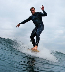 Rob Bird hanging five on his longboards surfing at Widemouth Bay