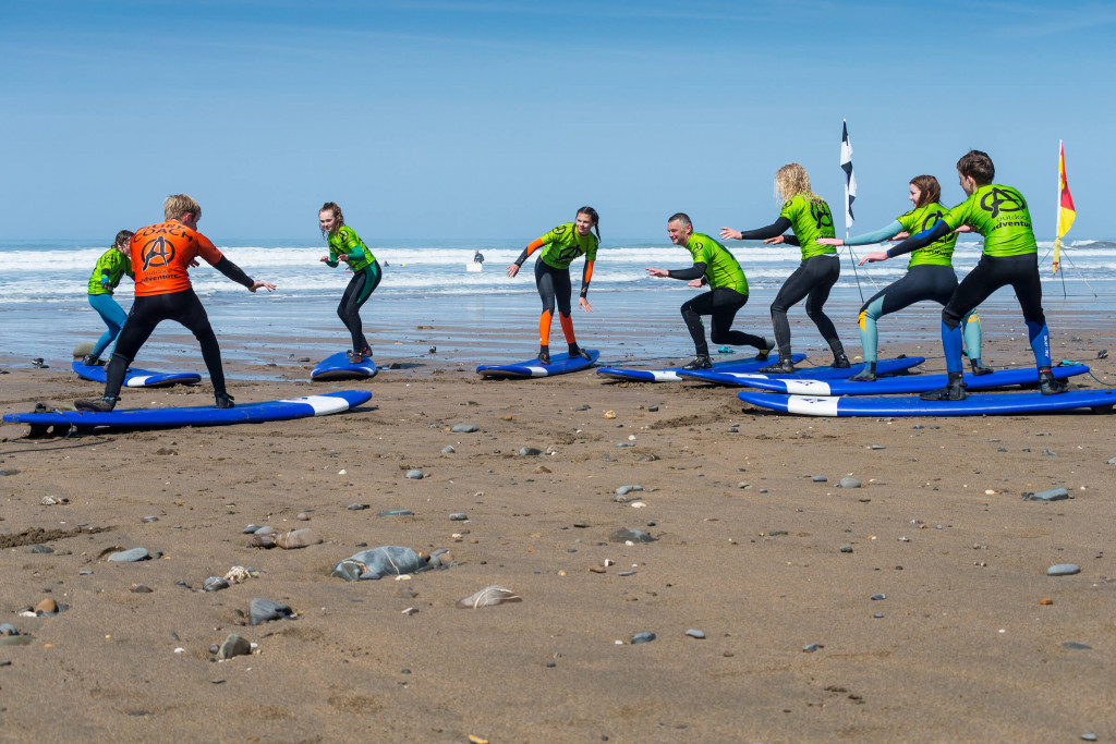 A beginner surf lesson having coaching on the beach at Widemouth Bay