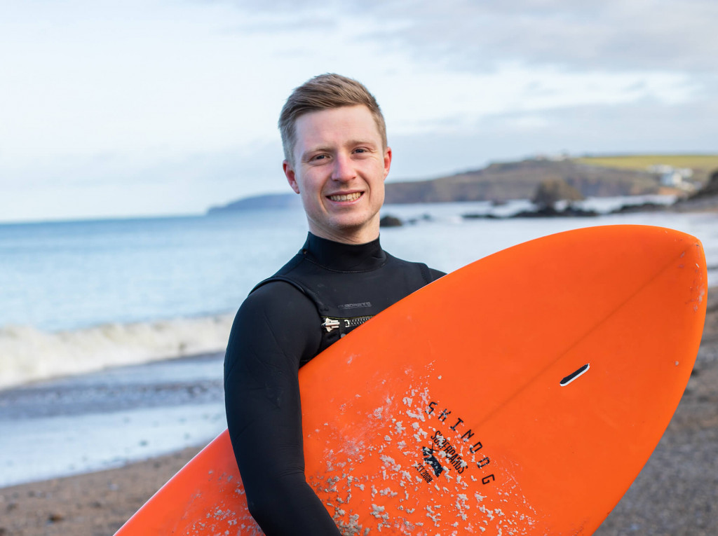 oa surf club team member lewis holding surf board at beach