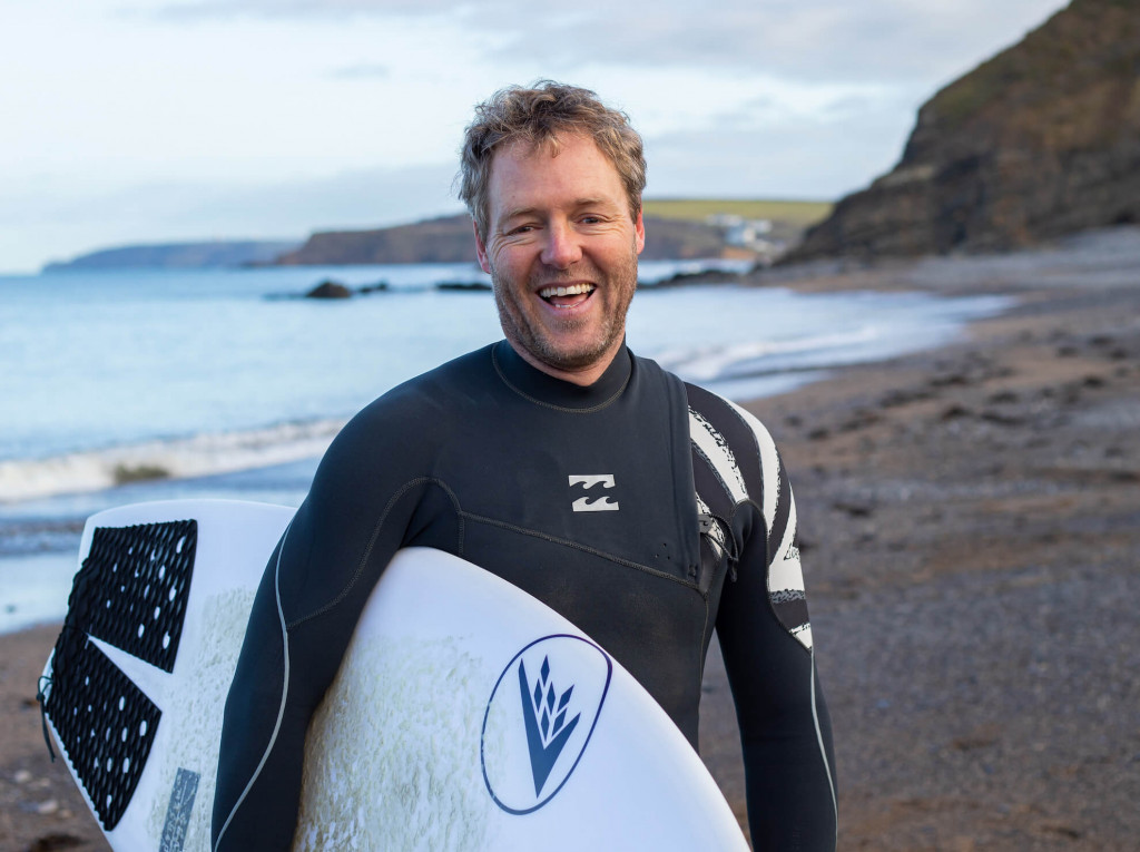 oa surf club team member rob holding surf board at beach