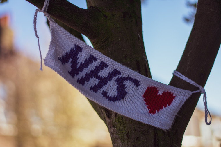 Knitted NHS sign with love heart, hung in a tree.