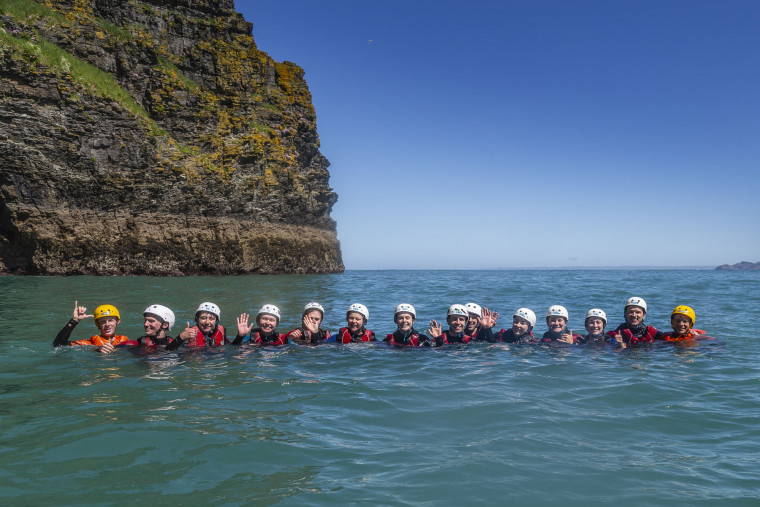 Group coasteer session lined up in the water.