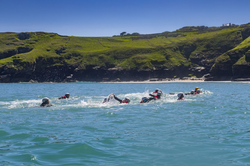 A group coasteering swimming in the sea.