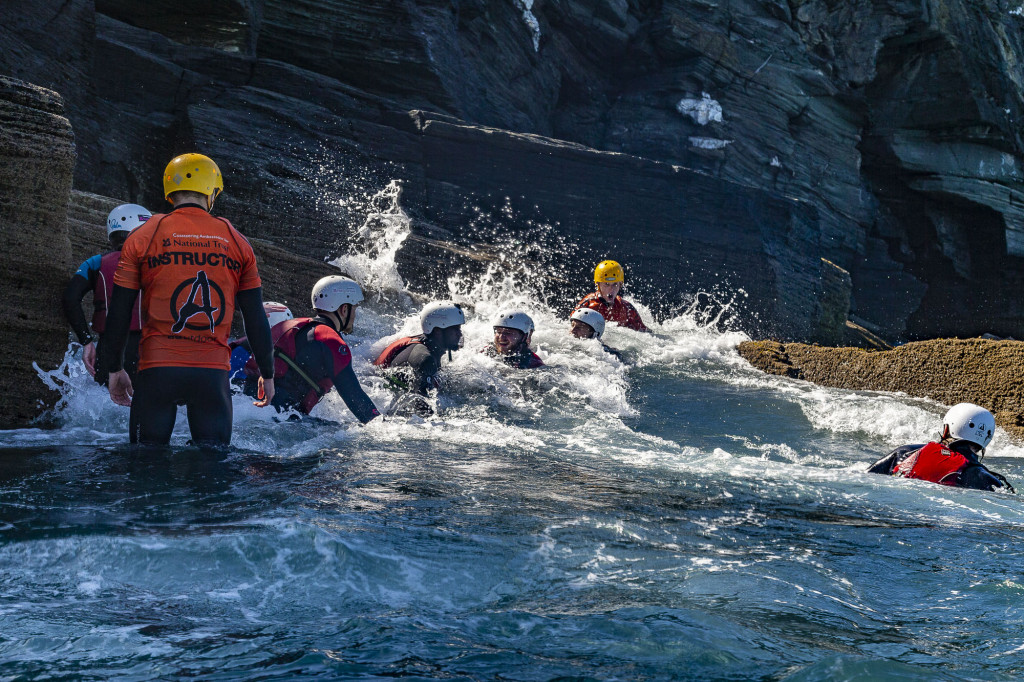 A costeering group playing in a feature, (the movement of the water where the swell hits the rocks).