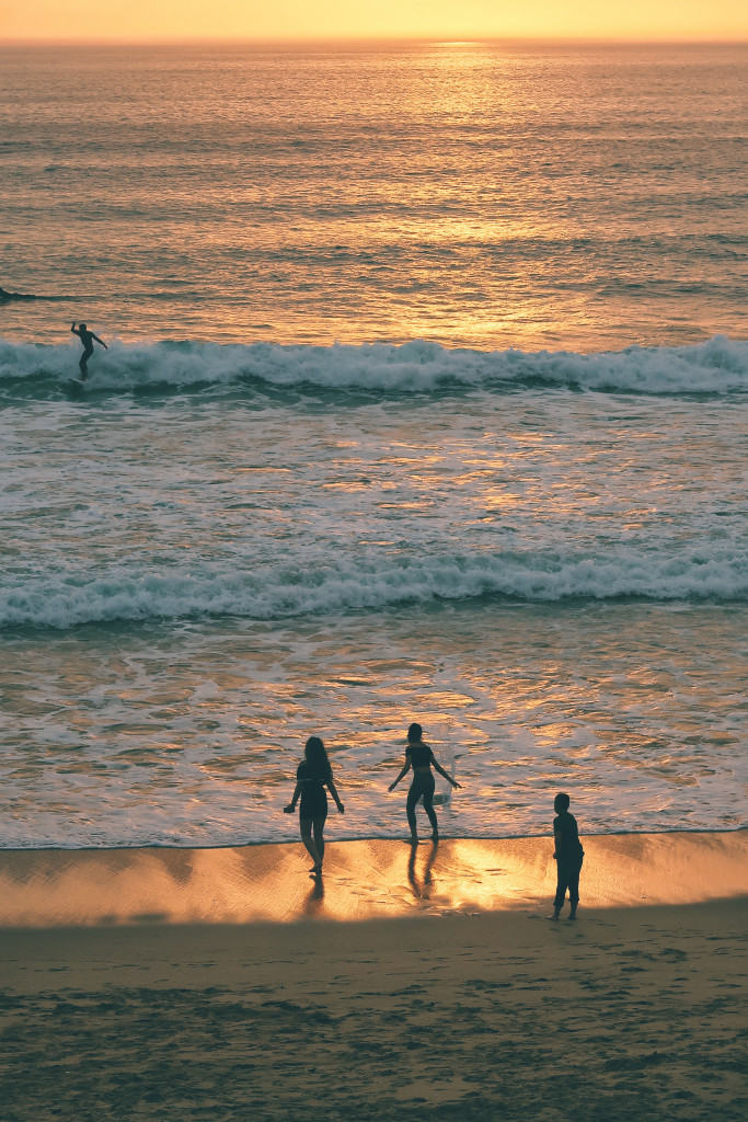 Sunset beach scene, with people playing in the sea.