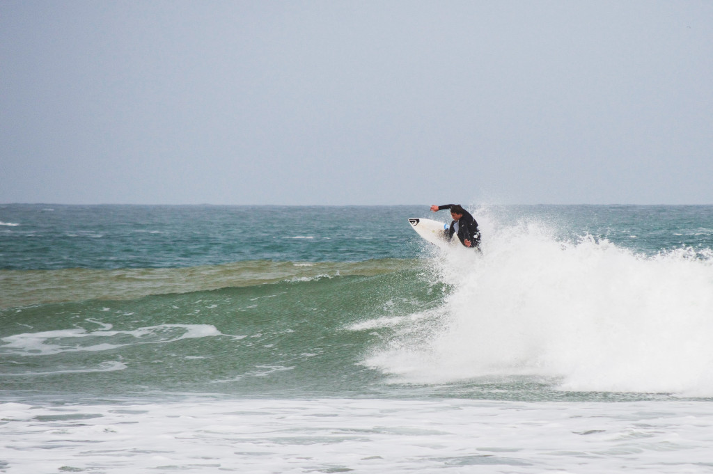 Surfer completing a top turn on a wave.