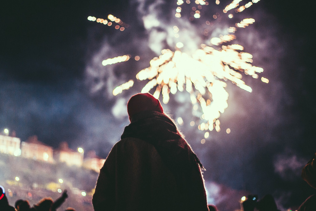 Someone standing and watching a fireworks display.